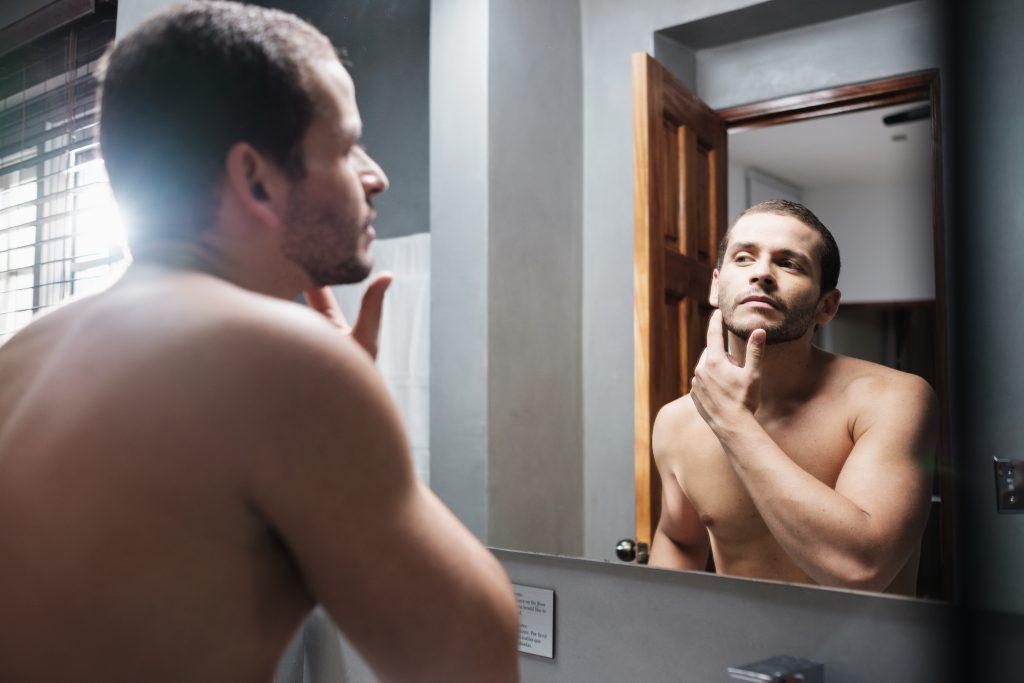 Mies katsoo peiliä mielessä parran siirto