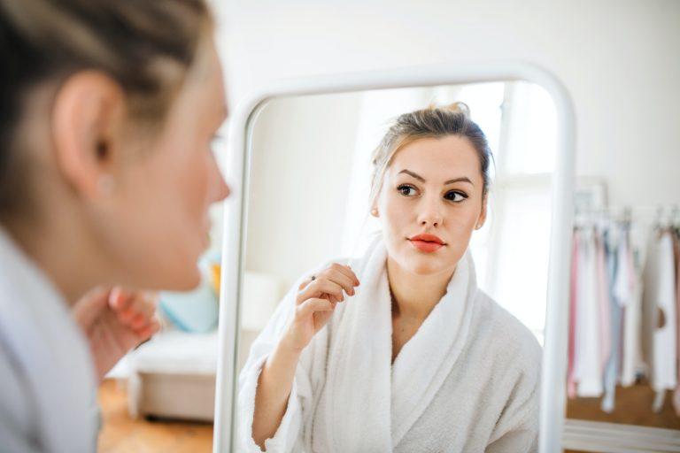 Young woman indoors at home in the morning, looking in mirror.