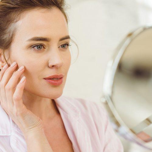 beautiful woman looking at her skin in mirror
